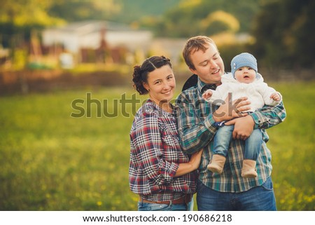 Portrait of a Young happy family having fun at countryside outdoors. Summertime. Family feeding Horses on the meadow - stock photo