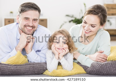 Portrait of a young, happy family lying on a sofa, with a little blonde boy between his parents - stock photo
