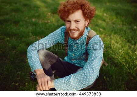 Portrait of a young happy ginger man relaxing on the grass - stock photo