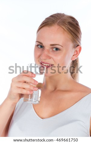 Portrait of a young happy girl holding a glass of water after fitness, isolated on a white background