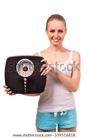 Portrait of a young happy girl holding weight and smiles, isolated on a white background - stock photo