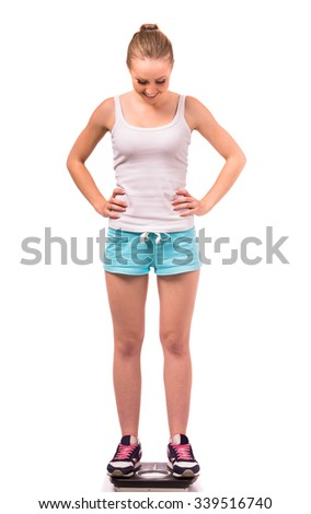 Portrait of a young happy girl standing on the scales, isolated on a white background - stock photo