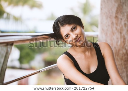 Portrait of a young happy indian woman in the morning relaxing at the balcony of the building - stock photo
