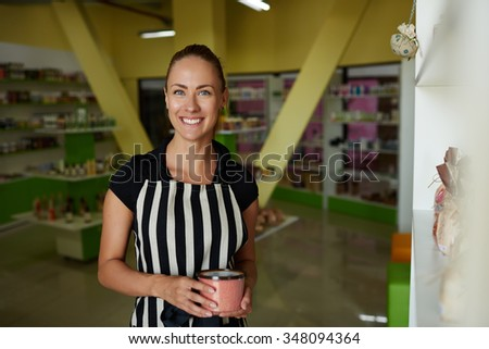 Portrait of a young happy saleswoman holding cosmetics product during work day in  beauty shop, gorgeous female consultant with beautiful smile posing while standing in drugstore or pharmacy - stock photo