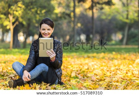 Portrait of a young happy smilling woman with a tablet sitting in a yellow autumn forest.