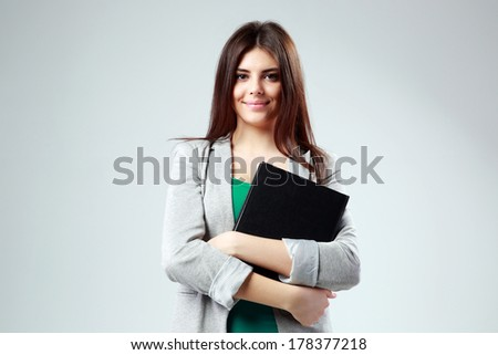 Portrait of a young happy student woman with book on gray background - stock photo