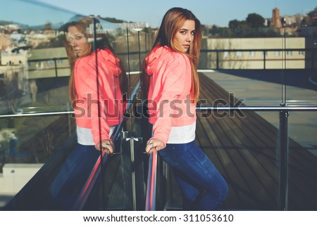 Portrait of a young hipster girl with long hair posing for the camera outdoors, glamorous female model dressed in stylish clothing enjoying sunny day outside, attractive hipster girl posing outside - stock photo