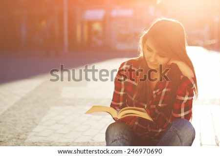 Portrait of a young hipster woman enjoying a good book sitting at sunny evening outdoors - stock photo
