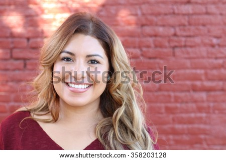 Portrait of a young Hispanic female smiling - stock photo