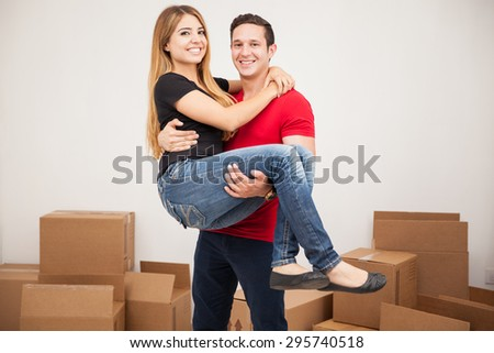 Portrait of a young Hispanic man carrying her wife into their brand new home - stock photo
