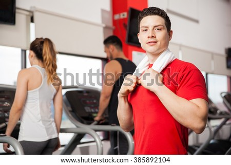 Portrait of a young Hispanic man with a towel on his neck, taking a break after doing some cardio in a gym - stock photo