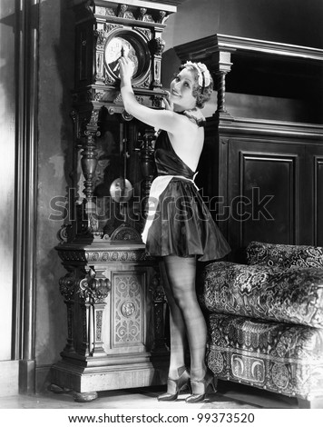 Portrait of a young house keeper adjusting time on a clock - stock photo