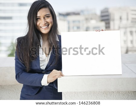 Portrait of a young Indian businesswoman holding sign - stock photo