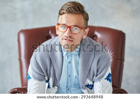 Portrait of a young intelligent man stares into the camera, good view, small unshaven, charismatic, wearing glasses rimmed with brown, blue shirt, gray sweater, sitting on a brown leather chair - stock photo