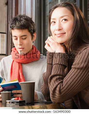 Portrait of a young Japanese couple sitting down at a cafe shop terrace taking a break in the city of London while on vacation, drinking a cup of hot coffee and reading a travel guide book, outdoors.