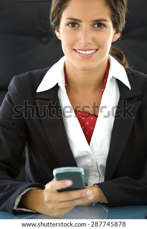 Portrait of a young Latin businesswoman at workplace with smart phone in hand - stock photo