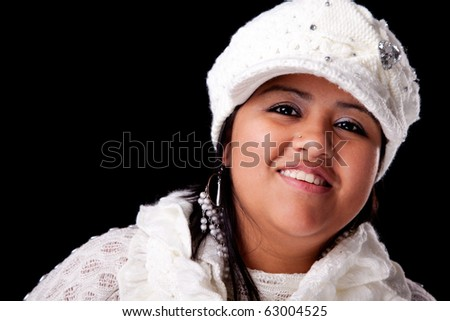 Portrait of a young latin woman smiling, in autumn/winter clothes, isolated on black. Studio shot