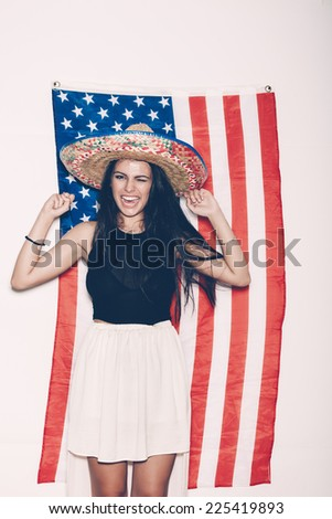 Portrait of a young Latina girl in sombrero having fun on the background of the American flag. Portrait on white background, not isolated