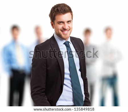 Portrait of a young leader in front of his team - stock photo
