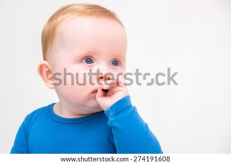 Portrait of a young little baby boy with blue eyes and red hair,  staring to the right with his fingers in his mouth, on a white background.  - stock photo