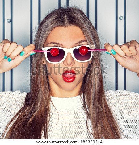 portrait of a young long-haired beautiful girl is holding two red lollipops in front of the white sunglasses - stock photo