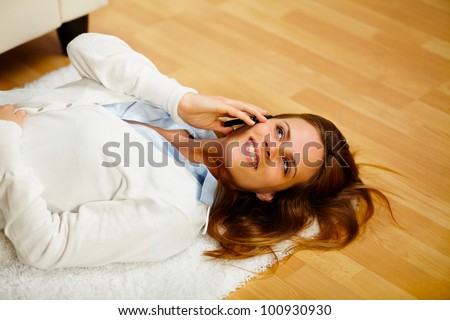 Portrait of a young lovely woman making a call on the cell phone while lying on the floor - stock photo