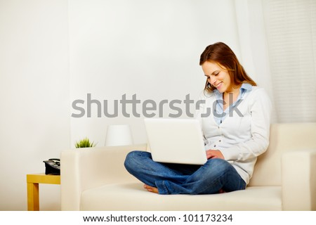 Portrait of a young lovely woman working on laptop at home