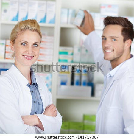 Portrait of a young male and female pharmacists smiling in front of medicines at drugstore