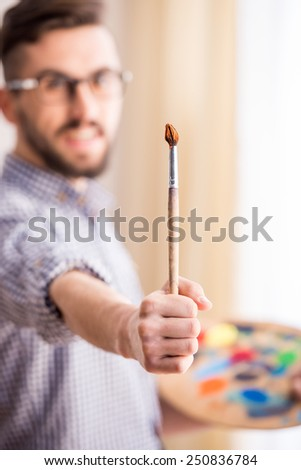 Portrait of a young male artist is holding a brush and mix color oil painting on palette. - stock photo