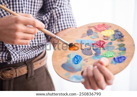 Portrait of a young male artist is holding a brush and mix color oil painting on palette. Close-up. - stock photo