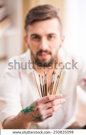 Portrait of a young male artist with brushes for painting. - stock photo