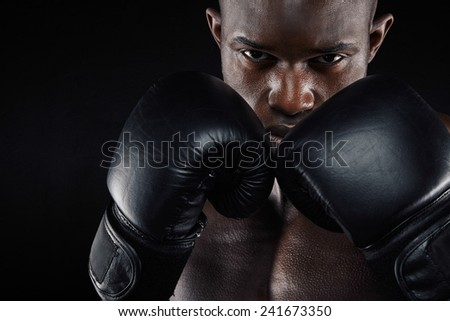 Portrait of a young male boxer in a fighting stance on black background. Young man doing boxing exercise. - stock photo