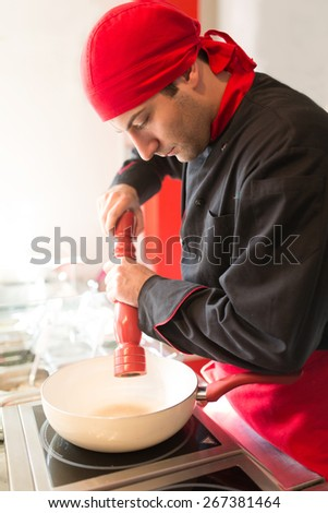 Portrait of a young male cook spicing a meal - stock photo