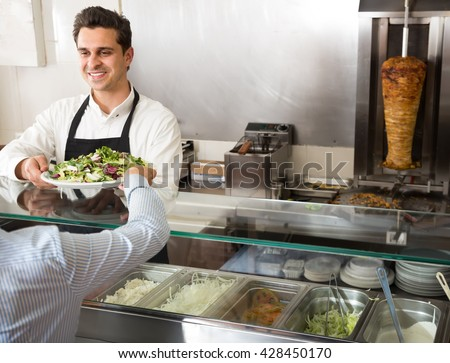 portrait of a young male fast food worker at counter of kebab cafe - stock photo