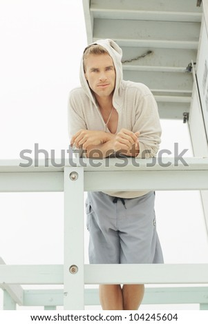 Portrait of a young male model in board shorts and warm pullover relaxing in outdoor beach setting