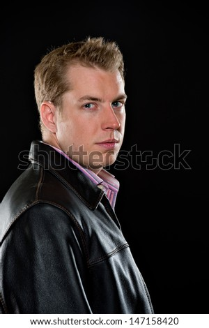Portrait of a young male model wearing a black leather jacket and colorful striped shirt.  He has a serious expression and is shot on a black background.