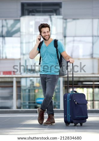 Portrait of a young male traveler talking on mobile phone - stock photo