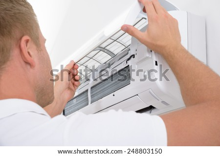Portrait Of A Young Man Adjusting Air Conditioning System - stock photo