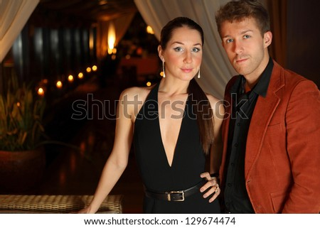 portrait of a young man and a brunette on a dark background - stock photo
