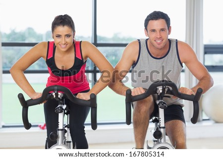Portrait of a young man and woman working out at class in gym