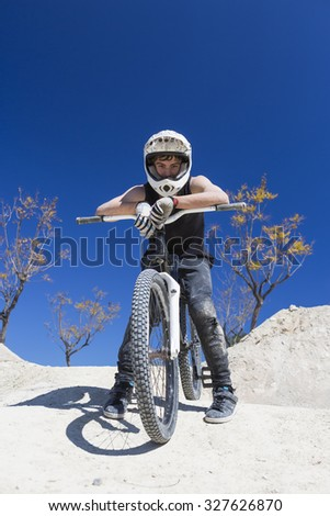 portrait of a young man BMX biker resting sitting on his bike on a BMX session in the mountain - focus on the face - stock photo