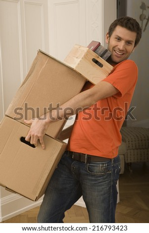 Portrait of a young man carrying cardboard boxes and smiling