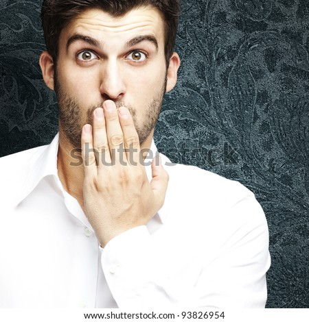 portrait of a young man covering his mouth against a vintage wall - stock photo