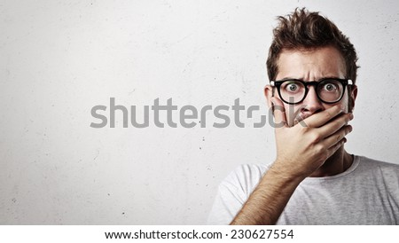 Portrait of a young man covering his mouth with hand - stock photo