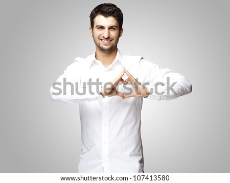 portrait of a young man doing a heart gesture against a grey background - stock photo