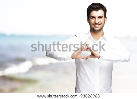 portrait of a young man doing a heart gesture against a sea background