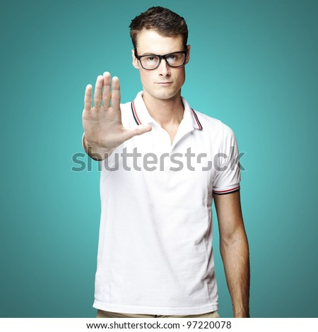 portrait of a young man doing a stop gesture over a blue background