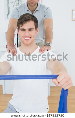 Portrait of a young man doing exercises with the help of therapist in the medical office - stock photo