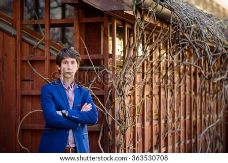 portrait of a young man dressed in a blue coat against wooden door - stock photo