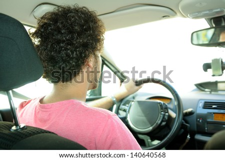 Portrait of a young man driving a car - stock photo